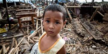 Kirby, four, stands amongst the debris where his house once stood before it was destroyed by typhoon Haiyan, Philippines. Photo Credit: Jonathan Hyams/Save the Children 2013