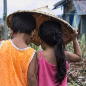 A boy and a girl, Noel, four and Roshel three, walk through their village in Dolores, Eastern Samar, Philippines, after Typhoon Hagupit tore through the region, in 2014. Many lost their homes and were without bare essentials. Save the Children has been distributing household kits, hygiene kits, water kits and emergency shelter kits to the most vulnerable families affected by the typhoon in the province of Samar. Photo credit: Jonathan Hyams/Save the Children, June 2016.