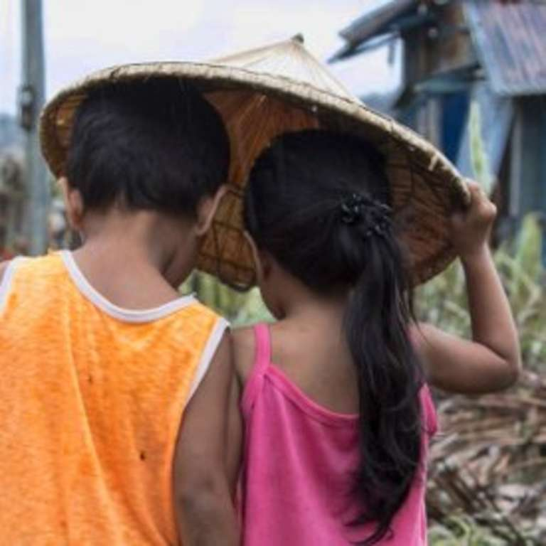 A boy of four and a girl of three walk through their village in Dolores, Eastern Samar, Philippines, after Typhoon Hagupit tore through the region, leaving many with destroyed homes and without bare essentials. Photo Credit: Jonathan Hyams/Save the Children 2014.