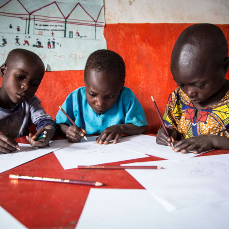 Three boys concentrate on their drawings at an Early Childhood Care and Development (ECCD) center in Burera, Rwanda. Their drawings depict a story from a book provided through Save the Children's support. These structured sessions of being read to – and drawing their interpretations of the story – are part of early literacy activities featured in Save the Children's Signature Education Program. Photo credit: Colin Crowley / Save the Children, March 2014.