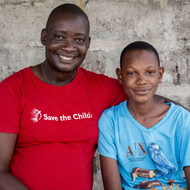 Child protection officer, Konday Marah, and 16-year-old Ebola survivor Joshua* sit outside a Save the Children field office in Sierra Leone. Thanks to the regular visits with Konday and our work to help reintegrate children who have survived Ebola back into society, Joshua's life is returning to that of a typical 16-year-old boy. Photo Credit: Jonathan Hyams/Save the Children 2015.