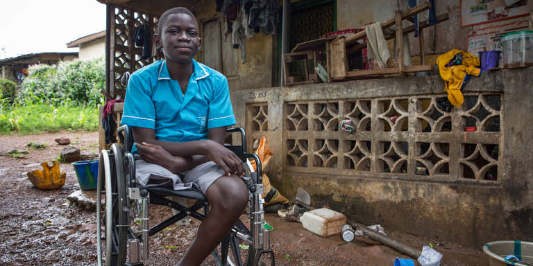 Samuel*, 15, sits in his new wheel chair provided by Save the Children, near his home in Freetown, Sierra Leone. His leg was amputated after a life-threatening infection during the Ebola crisis. Photo credit: Jonathan Hyams/Save the Children 2015.