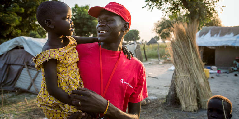 A Save the Children child protection officer, Bol Tyuol, holds a 6-year-old girl at her grandmother's home in South Sudan. The girl and her brother have been living there since violence broke out in December of 2013 and they became separated from their mother. Photo credit: Jonathan Hyams / Save the Children Foundation, November 2015.