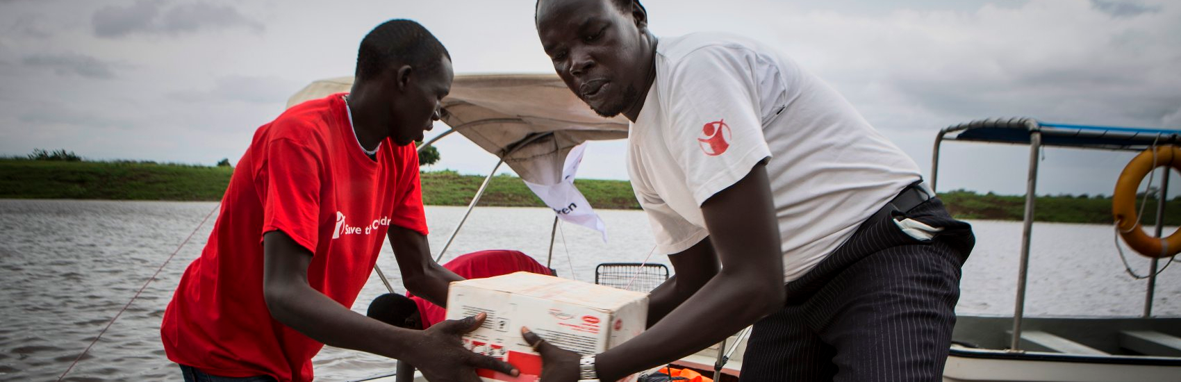 Save the Children field staff offloading a boat with food supplements for malnourished children in remote villages in Akobo, South Sudan. Photo Credit: Jonathan Hyams/Save the Children 2014.
