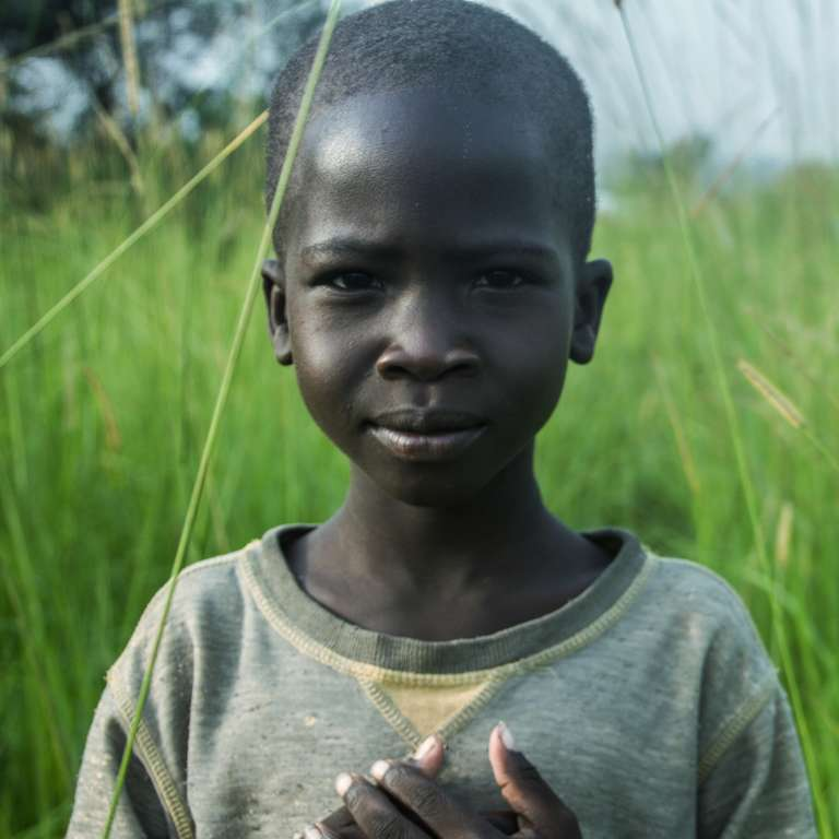 Portrait of a young boy, age 7, on his way back home after playing at a Save the Children child-friendly space in Uganda. The boy had to flee his home in South Sudan due to extreme violence and ongoing conflict. Photo Credit: Mark Kaye/Save the Children, July 2014.