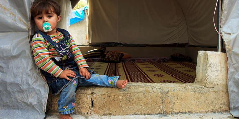 A two-year-old girl sits on the floor of her family's tent in a camp for displaced people on the northern Syrian border. Photo credit: Ahmad Baroudi/Save the Children, May 2015.