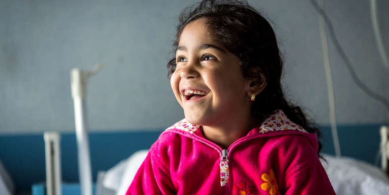 A five-year-old from Syria, plays in her hospital bedroom where she was treated for asthma after being rescued by the Save the Children vessel in the Mediterranean Sea near the coast of Italy. Photo Credit: Louis Leeson/Save the Children 2016.