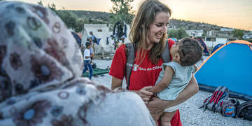 A Save the Children staff member greets a Syrian family in Lesvos, Greece after they've made the perilous journey across the Mediterranean Sea. Photo credit: Save the Children, February, 2017.