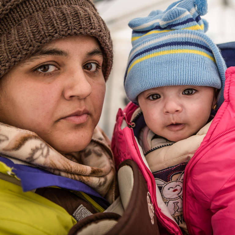 Rabia and her daughter Yasmin take shelter from the snow and freezing temperatures in a tent with their family. Photo credit: Jonathan Hyams/Save the Children, January 2016.