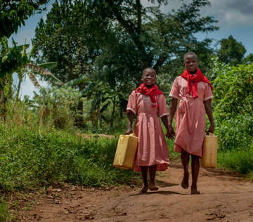 A girl and her friend holding water containers in Uganda.
