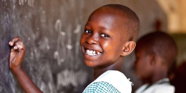 A 9-year-old schoolgirl in Uganda smiles brightly as she practices writing numbers on a chalkboard in her classroom. Photo credit: Jordan. J. Hay, 2012.