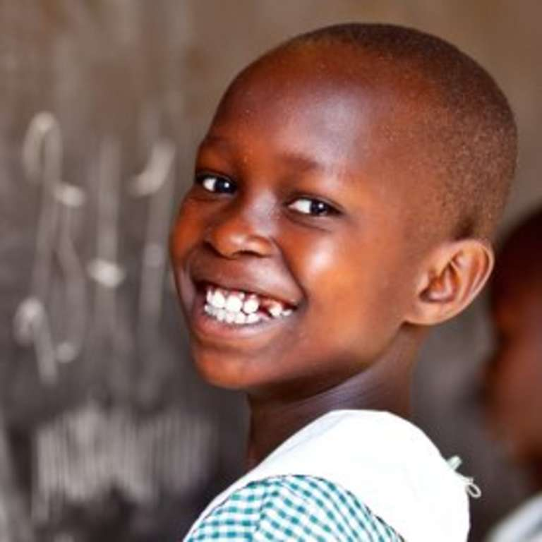 A 9-year-old schoolgirl in Uganda smiles brightly as she practices writing numbers on a chalkboard in her classroom thanks to a charity for children's education. Photo credit: Jordan. J. Hay, 2012.
