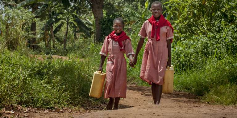 Two young girls fetch water together in Uganda. Photo Credit: Rick D'Elia/Save the Children 2016