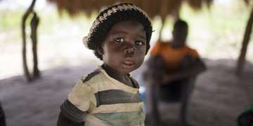 A baby boy stands at the border between South Sudan and Uganda.