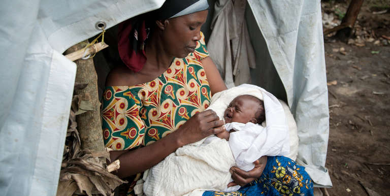 A foster mother, Theresa, cradles a newborn in a refugee settlement of Rwamwanja, Uganda. Theresa has 3 children of her own, but is helping care for the baby and her 5 siblings after the mother died from childbirth complications. The children's father – a solider – was in a military hospital after being shot in the leg amid violence in the Democratic Republic of the Congo. Photo credit: Rebecca Vassie/Save the Children, March 2014.