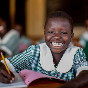 A young girl, age nine, shares a happy smile as she writes in her notebook at a Save the Children-sponsored school in Uganda. Save the Children is expanding our education programs throughout the country so that more hard-to-reach Ugandan children can attend and remain in school. Photo Credit: Jordan J. Hay/Save the Children, April 2012.