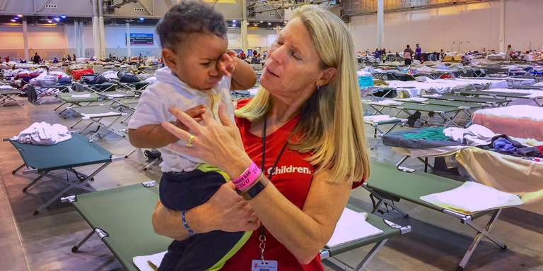 Carolyn Miles, president & CEO of Save the Children meets with families in a mega-shelter in Houston, Texas. Photo Credit Susan Warner/Save the Children 2017.
