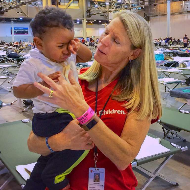Carolyn Miles, President and CEO of Save the Children comforts a 10-month old boy on a cot in a mage-shelter in Houston in the aftermath of Hurricane Harvey. Save the Children distributed cribs and other essential supplies to families in the shelter. Photo credit: Susan Warner/Save the Children, September 2017.