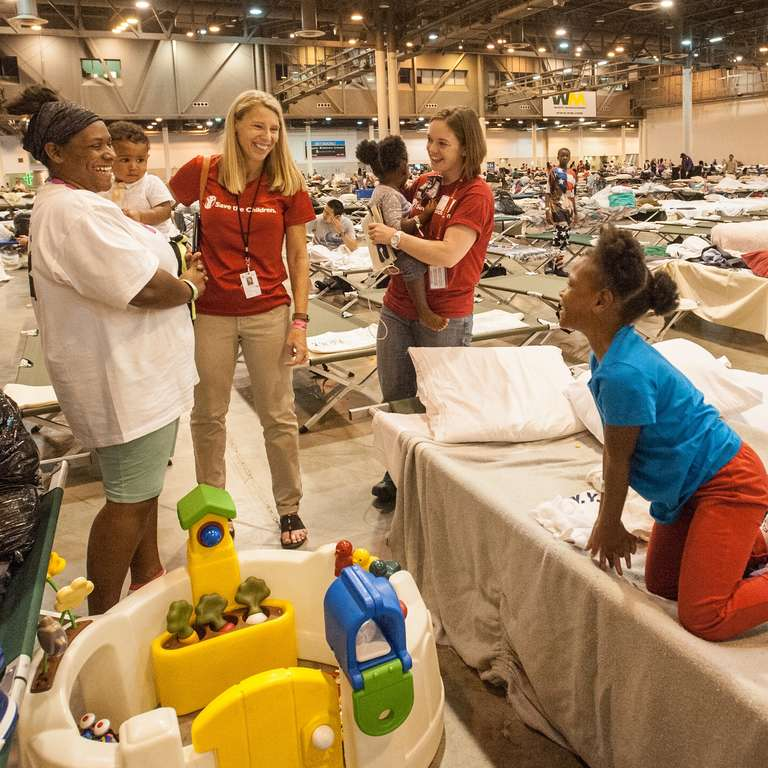 Carolyn Miles, president & CEO of Save the Children, and Erin Taylor, Save the Children staffer, meet with children and families at a mega-shelter in Houston, Texas. Photo Credit: Susan Warner/Save the Children 2017.