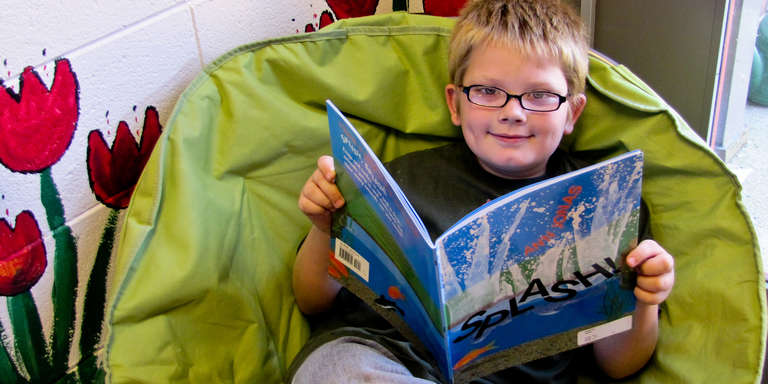 Timmy, age 8, relaxes in a cozy chair with a book. He is learning to read and loving it, thanks to Save the Children's U.S. Literacy programs in Kentucky. Photo credit: Save the Children, January 2012.