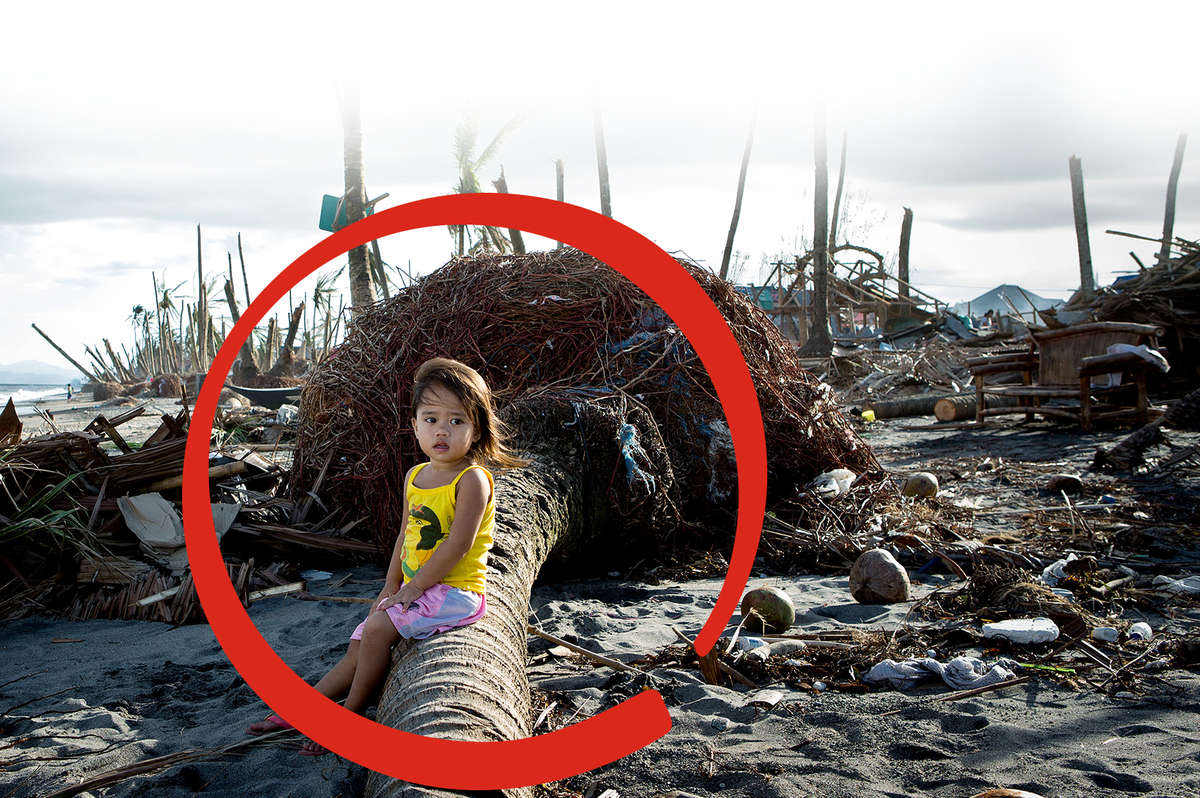 Gillian, two, sits on a log amongst the debris where her village once stood. It was destroyed by typhoon Haiyan, which struck the Philippines in 2013. Many coastal villages were devastated by the storm, and debris blocking roads made access impossible. Save the Children was on the ground expanding operations to deliver life-saving aid and medical care across the Leyte province. Photo credit: Jonathan Hyams/Save the Children, November 2013.