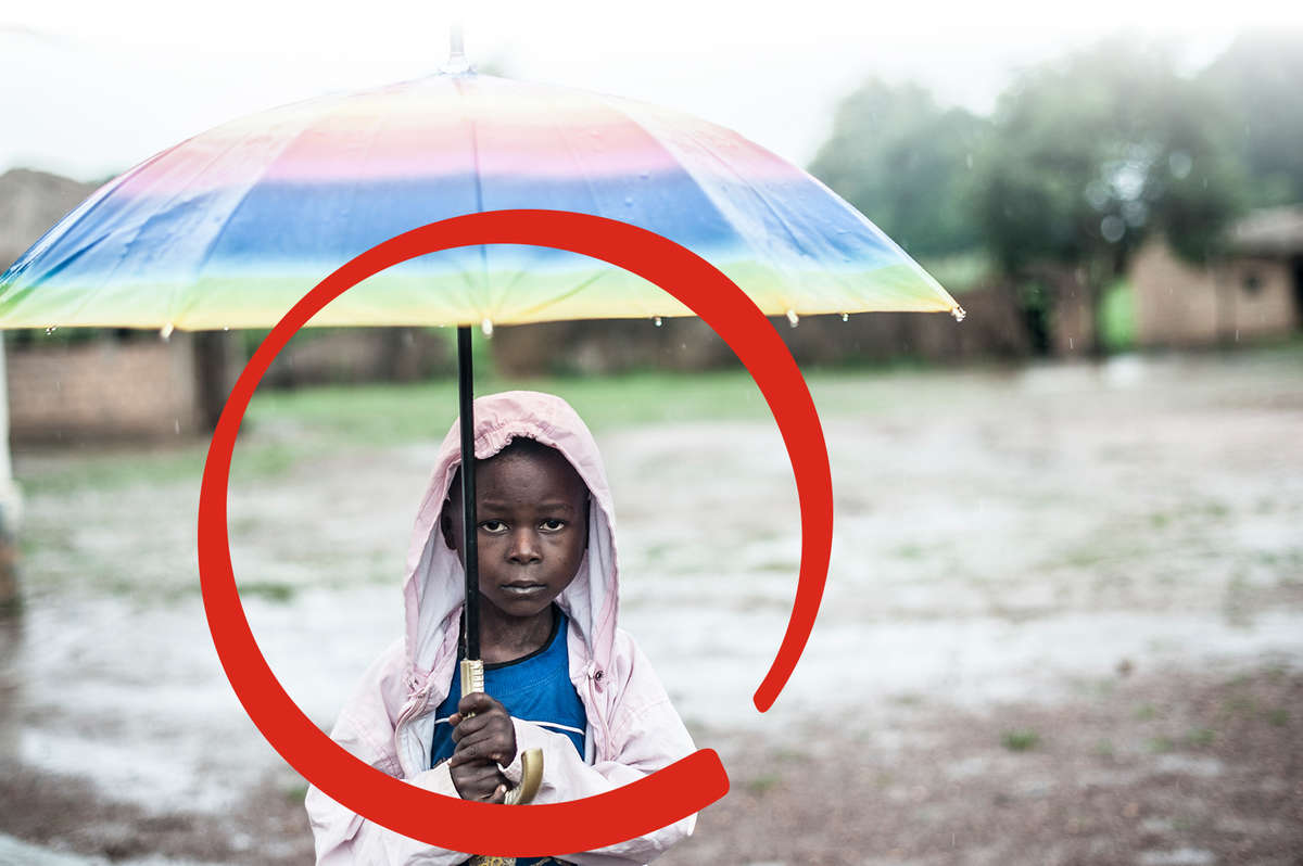 Young Bienvenu, a boy from Central African Republic, stands holding an umbrella in the rain. He was recently treated for malaria by a Save the Children medical team. He and his brother are living with an aunt in a small mud house after having to flee violence in their area. Struggling to make ends meet, the family received basic provisions and some financial assistance from Save the Children, and the children are being monitored for malnutrition. Photo credit: Sylvain Cherkaoui/ Cosmos/Save The Children, June 2015.