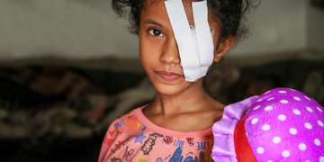 A girl with a bandage over her eye looks into the camera.