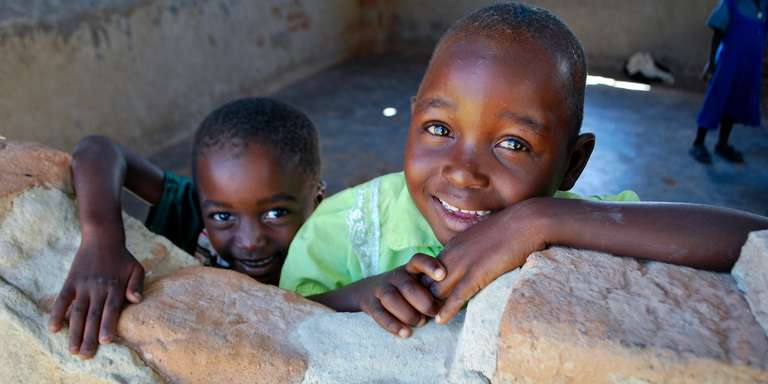 "Two children look out the ""window"" at the Early Childhood Center in a village in Zimbabwe. Photo Credit: Eileen Burke/Save the Children 2011."