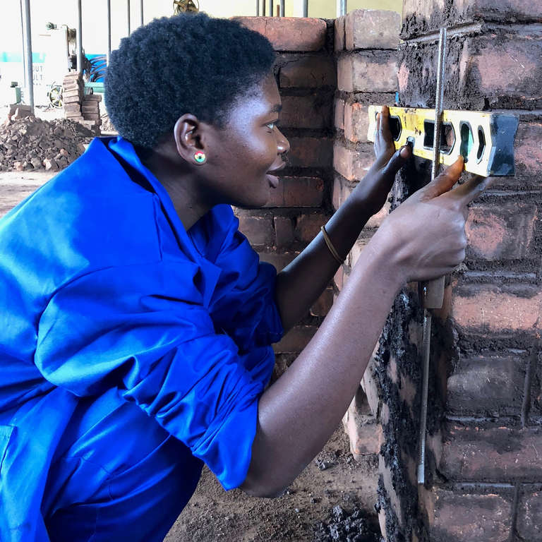 A young girl practices using a level at a Save the Children vocational program in Malawi. Photo credit: Save the Children, 2017.