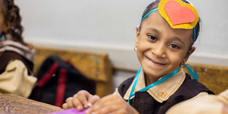 Seven-year-old Sara wears a colorful headband made from ribbon and paper hearts. They were distributed to students during Welcome Month, a basic education activity aimed at reducing dropout rates in government schools in Egypt. Photo credit: Victoria Zegler / Save the Children, October 2017.