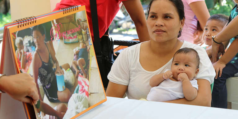 Michelle, a mother in the Philippines, learns how to best care for her baby Alyssa. Photo credit: Save the Children.