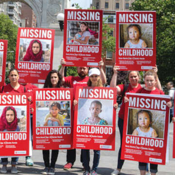 "A large group of Save the Children employees hold signs in Washington Square Park that show children's faces and read, ""Missing Childhood."" On International Children's Day, staff went to various public places with signs detailing the various ways in which children are missing out on their childhood. Photo credit: Ellery Lamm, June 2018."
