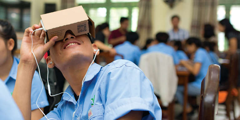 A young student in Vietnam looks though a VR google set for the first time. Photo credit: Roi Images/STUDIO at Getty Images for Accenture.