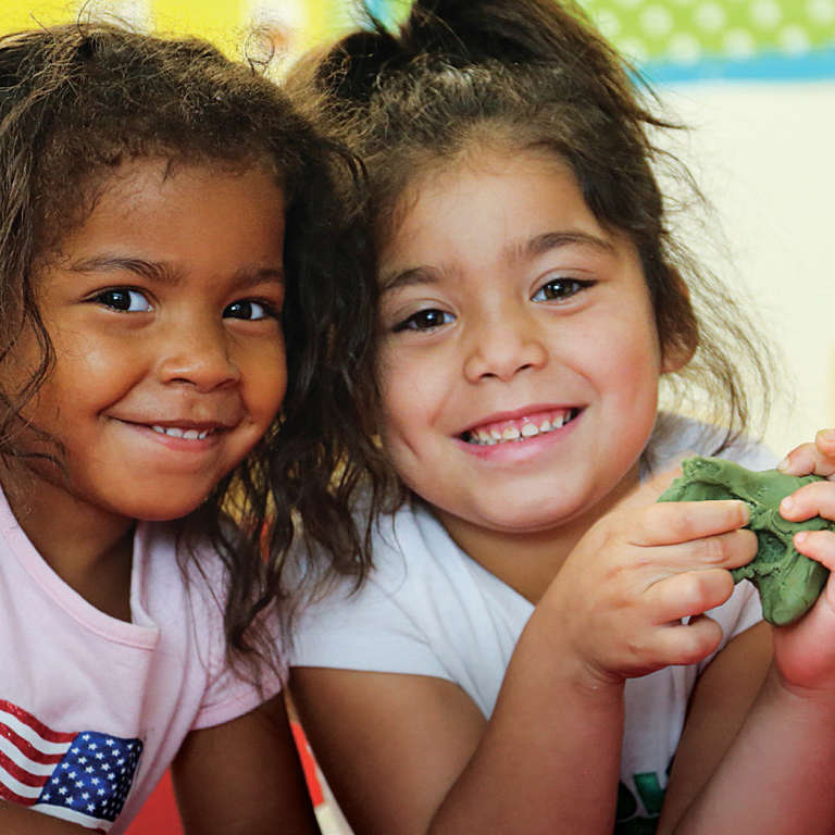 Two girls play with play-dough in their daycare in Texas. Their daycare was heavily affected by Hurricane Harvey in 2017. They sustained structural damage as well as damage to the interior, exteriors classroom equipment and playground equipment. Funds and GIK books and toys from Save the Children has helped and enhanced the quality of the day care and the children's day to day experience. Save the Children also replaced the restroom and the counters in the kitchen. Photo credti: Ellery Lamm/Save the Children 2018.