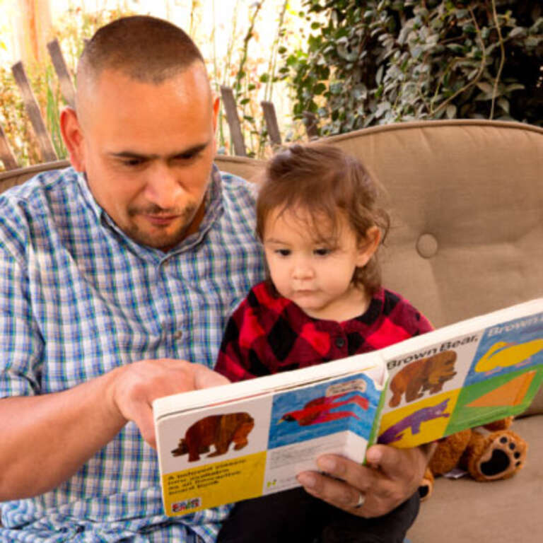 A father and his young daughter enjoy the popular children's book Brown Bear, Brown Bear together.]