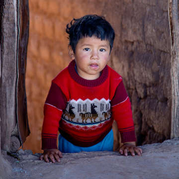 An unaccompanied child stands in a doorway.