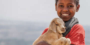A child poses with a goat that can provide milk for a family