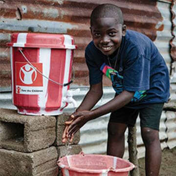 A boy washes his hands using a clean water kit.