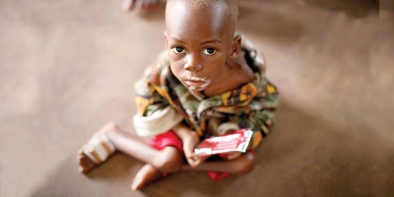 A young boy eats ready-to-use food for Save the Children's gift catalog. Photo credit: Save the Children 2017.