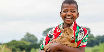 A boy holds a goat, which is available on the Save the Children gift catalog. Photo Credit: Save the Children 2017.