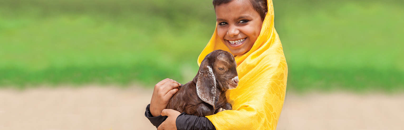 A young girl holds a baby goat for the Save the Children gift catalog. Photo credit: Save the Children 2017.