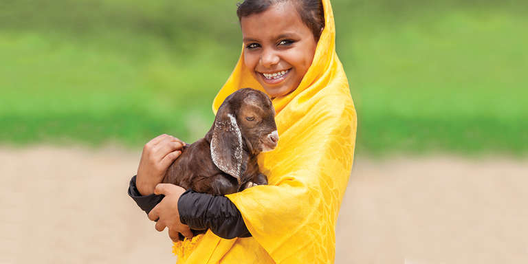 A young girl poses with a goat for Save the Children's gift catalog. Photo credit: Save the Children 2017.