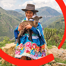 A young Peruvian girl holds a baby goat in her arms. Goats can provide a family nourishing, protien-rich dairy to satisfy hungry children. Baby goats can be sold to help families pay for other essentials, like school and medicine. Photo credit: Jonathan J. Hay / Save the Children, April 2018.
