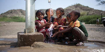 A group of children play in a water spigot
