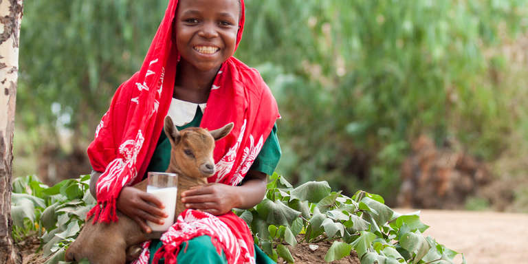 A schoolgirl sits holding a baby goat and a glass of milk. Goats can provide nourishing, protein-rich dairy to satisfy hungry children – and baby goats can be sold to help pay for essentials like school or medicine. Learn more how you can send a goat to a family in need. Photo credit: Save the Children, 2017.