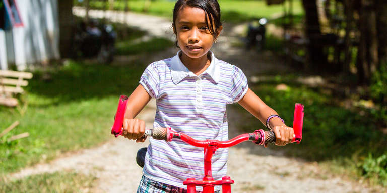 A 9-year-old girl rides a red bicycle outside her home in in West Sumba, Indonesia. Photo credit: Victoria Zegler / Save the Children, May 2017.