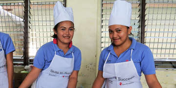 In Metro Manila, Philippines, Marilyn and Antonette, both 19 years old, prepare to serve their special guests  lunch. Photo credit: Save the Children 2014.