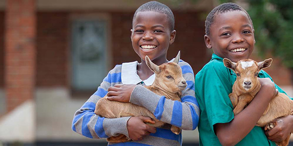 Two children smile while holding goats.