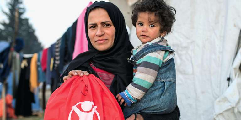 A mother in the middle east holds her child and a refugee basics bag from Save the Children relief efforts. Photo Credit: Save the Children 2016.