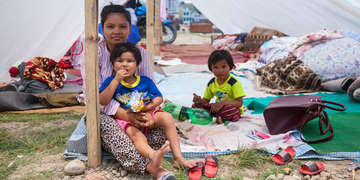 In Kathmandu a family shelter from the midday sun in their newly constructed tent. No one knows how long they should stay or when it will be safe. Photo credit: Save the Children 2015.